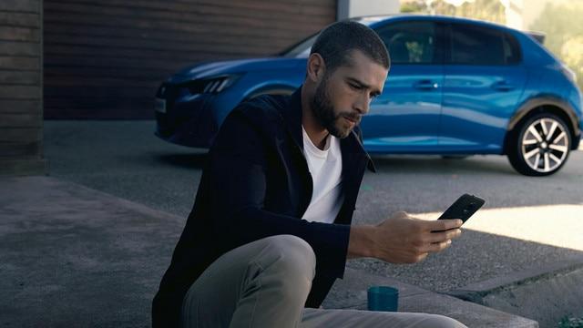 Nieuwe Peugeot e-208 - Man met smartphone, MyPeugeot App